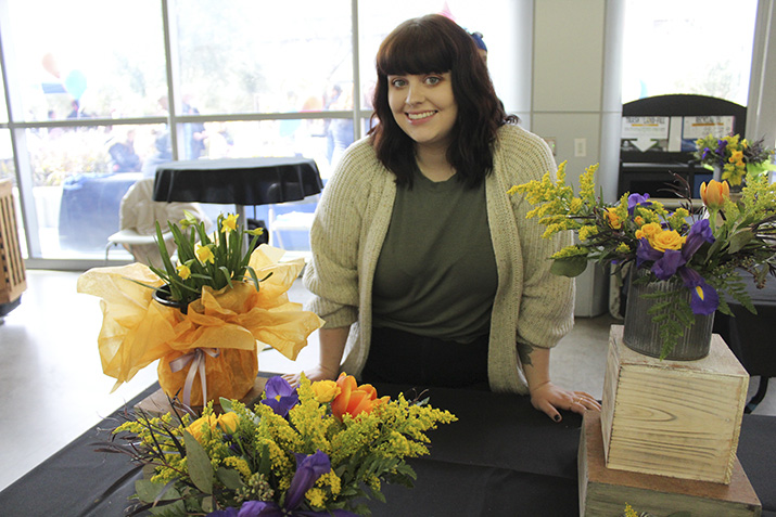 Christen Hollingsworth, an intern with the floriculture department, sells floral arrangements at the Horticulture Floral Sale on Feb. 7, 2019. (Photo by Ariel Caspar)