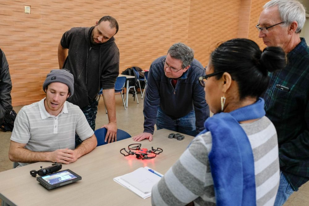 Students of the drone class, Experimental Offering in Design Technology, gather around Sean Franklin (left), who describes the various operations that are available in the drone unit they were flying in the Student Center at American River College on Feb. 2, 2019.