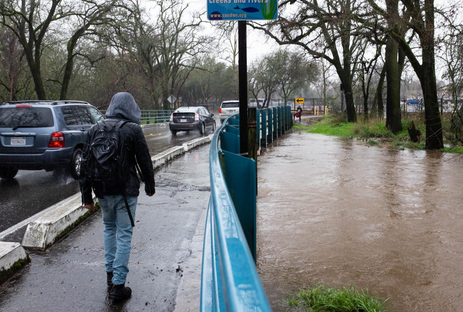 A student walks across the bridge over Arcade Creek as rain causes the creek to flood nearly over the ridge at American River College on Feb. 26, 2019. (Photo by Patrick Hyun Wilson)