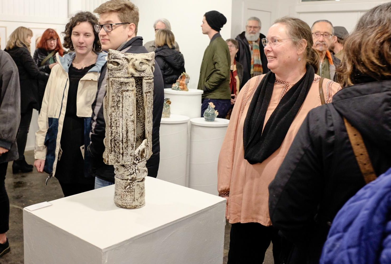 Photography professor Jodie Hooker admires the works of art made by her colegues during the opening reception for the ARC Faculty/Staff Art Show at the E Street Gallery on Feb. 10, 2019. (Photo by Patrick Hyun Wilson)