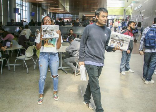 American River Current Social Media Editor Alexis Warren (left) poses with the latest edition of the American River Current while Sports Editor Gabe Carlos distributes in the cafeteria at American River College on March 18, 2019. (Photo by Hameed Zargry)