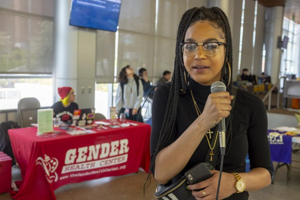 UNITE member Grace Swint, a political science and sociology double major, stands in front of booths for the week-long Womxn's Health Resource Fair in the Student Center at American River College on March 26, 2019. She, along with other UNITE members, helped organize the event which was combined with their bi-weekly Tell It Tuesday open mic. (Photo by Patrick Hyun Wilson)