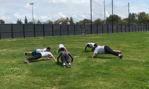 Students in the Boot Camp Fitness class, a class dedicated to putting students through various forms of exercise including strength and endurance training, do pushups as part of their workout near the tennis courts at American River College on March 28, 2019. (Photo by Alexis Warren)