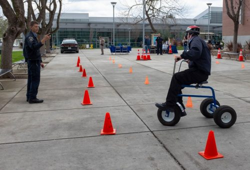 Outside the library at American River College, campus patrol officer John Lawyer rides a tricycle while wearing drunk goggles for the California Highway Patrol DUI Awareness tricycle obstacle course on March 20, 2019. (Photo by Patrick Hyun Wilson)