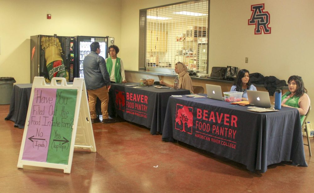 "A sign that reads ""Have you Filled Out the Food Intake Form?"" directs students on which table to go to when they visit the Beaver Food Pantry in the gym at American River College on March 27, 2019. (Photo by Emily Mello)"