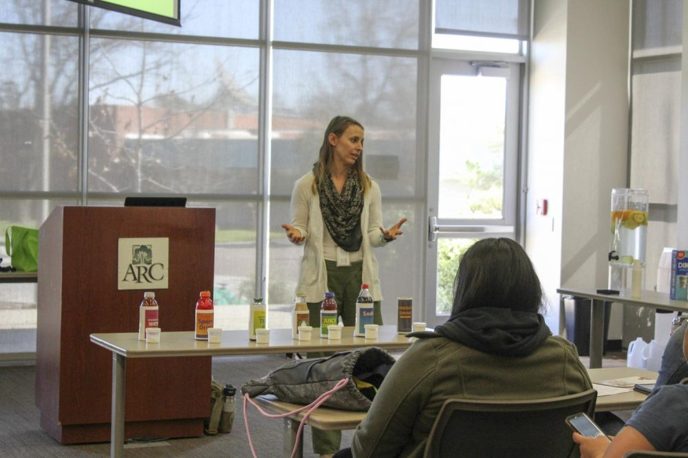 Angela Gibson from the Sacramento County Public Health Department rearranges different types of drinks from least to highest sugar content at Rethink Your Drink as part of American River College's spring 2019 Wellness Week on March 21, 2019. (Photo by Ariel Caspar)