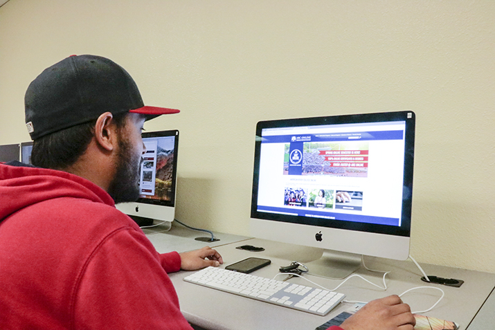 Gabe Carlos, sports editor for the Current, checks out the ARC Online 2.0 website in class at American River College on March 6. (Photo by Breawna Maynard)