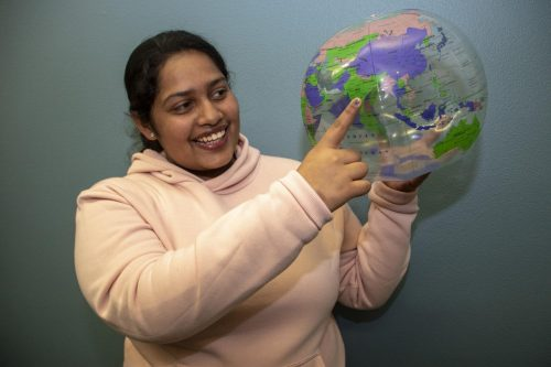 International student and business major Christina Abraham holds up a globe and points to India, where she's from, during an international student meetup at American River College on Jan. 31, 2019. (Photo by Ashley Hayes-Stone)