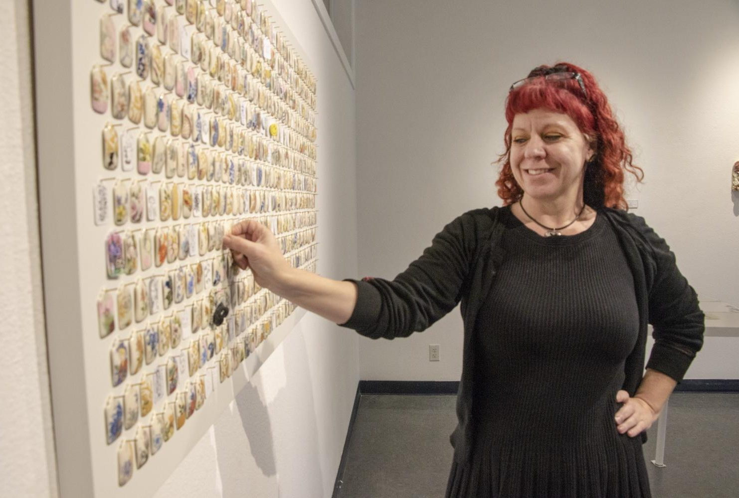 "Art major Frankie Vanity gazes at the porcelain tags that hang on the Kaneko Gallery wall at American River College on March 25, 2019. The porcelain tags are a part of artist Shenny Cruces' exhibition ""Managerie,"" where students choose and replace with their own art. (Photo by Ashley Hayes-Stone)"