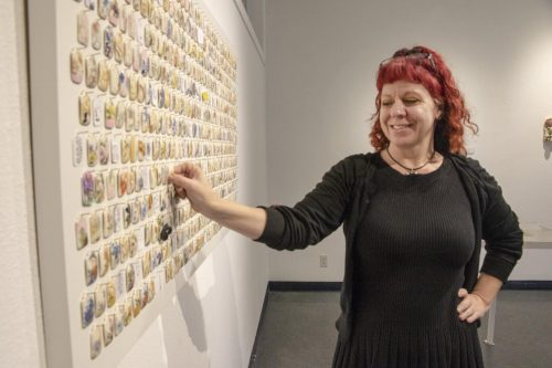 """Art major Frankie Vanity gazes at the porcelain tags that hang on the Kaneko Gallery wall at American River College on March 25, 2019. The porcelain tags are a part of artist Shenny Cruces' exhibition """"Managerie,"""" where students choose and replace with their own art. (Photo by Ashley Hayes-Stone)"""