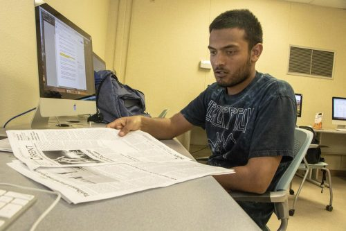 Gabe Carlos, sports editor of the American River Current, views proof pages of the upcoming print issue on April 8, 2019. The newspaper will come out this week on April 10th. (Photo by Ashley Hayes-Stone)