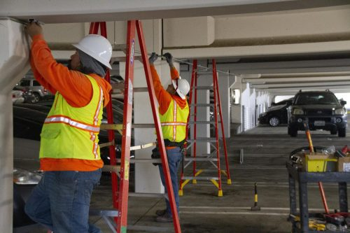 Derrick Camero and Billy Johnson, construction workers from Sebastian Corp, install security cameras in the parking structure as a part of a district wide update at American River College on April 2, 2019. (Photo by Jennah Booth)