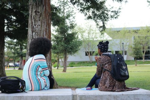 American River College students Chaiyah Wilson (left), Environmental Studies major, and Olive Muziranenge (right), Pediatric Nursing major, catch up with each other between classes on April 30, 2019. (Photo by Makenna Roy)