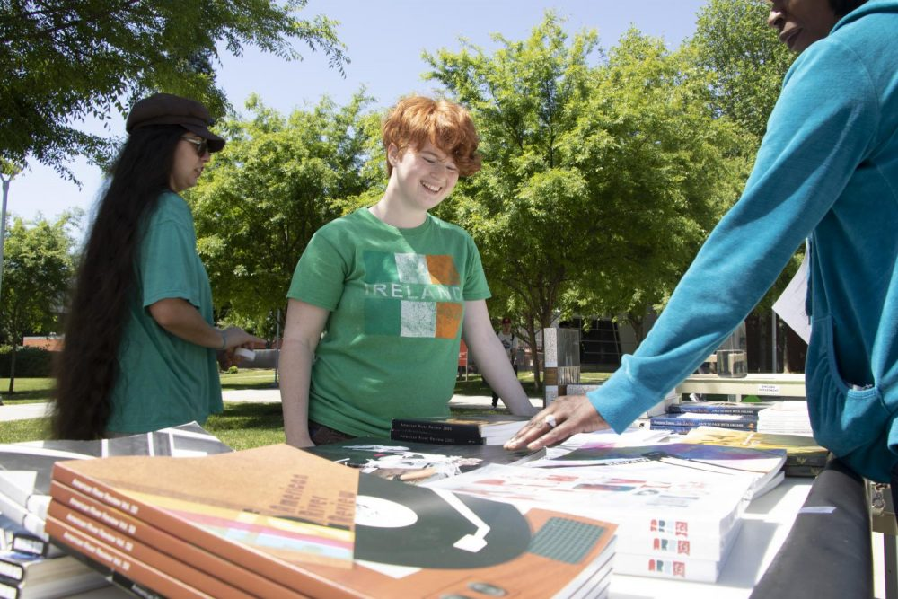 Kelsey Huffaker, administration of justice major, sells new and old American River Review literature magazines created by the Art New Media classes at American River College on May 2, 2019. (Photo by Imani Smith)