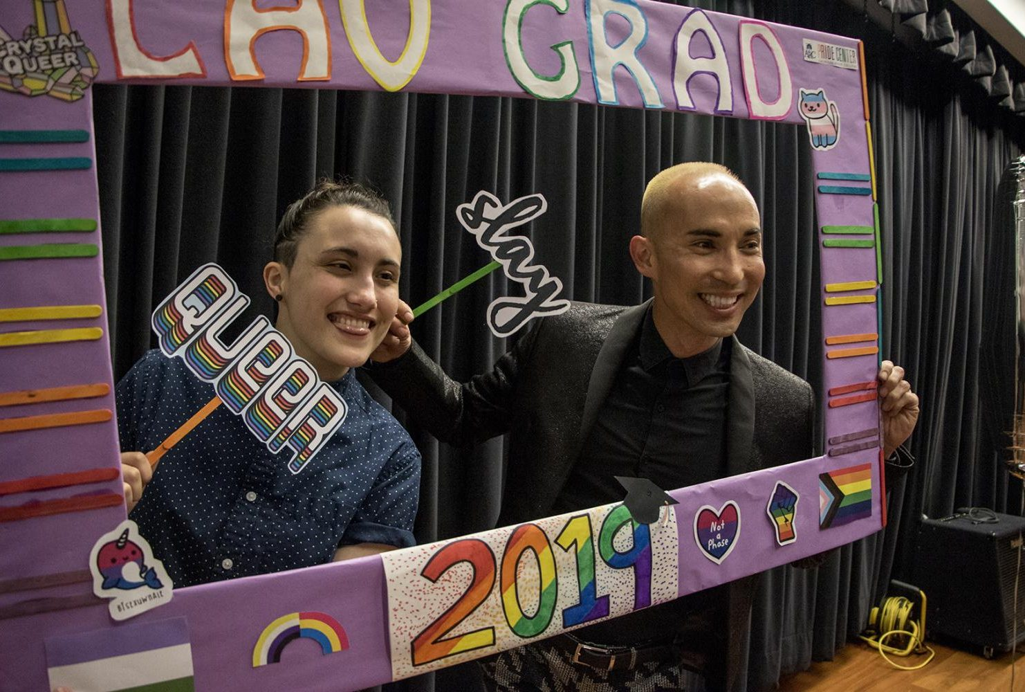 Pride Center student mentor Tori Miller and Equity Programs and Pathways Dean Joshua Moon Johnson pose with a prop frame at the ceremony on May 3, 2019. (Photo by Ashley Hayes-Stone)