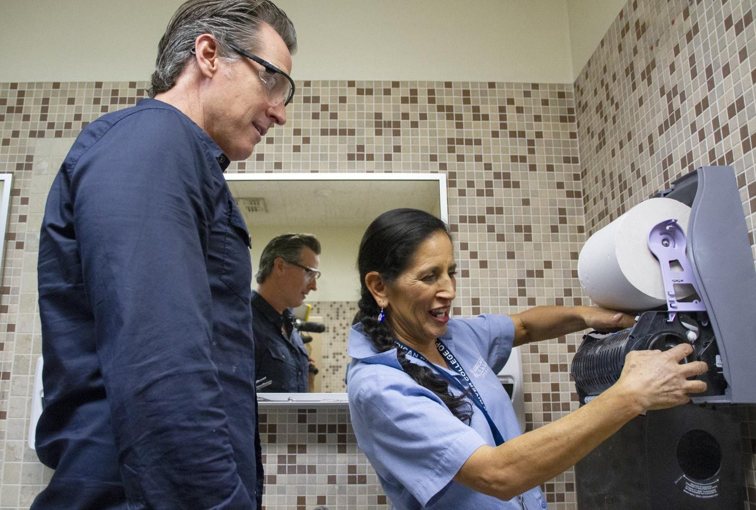 Calif. Governor Gavin Newsom shadows custodian Maria Arambula and replaces a paper towel dispenser in the restroom on the third floor of Davies Hall at American River College for international Workers' Day on May 1, 2019. (Photo by Patrick Hyun Wilson)