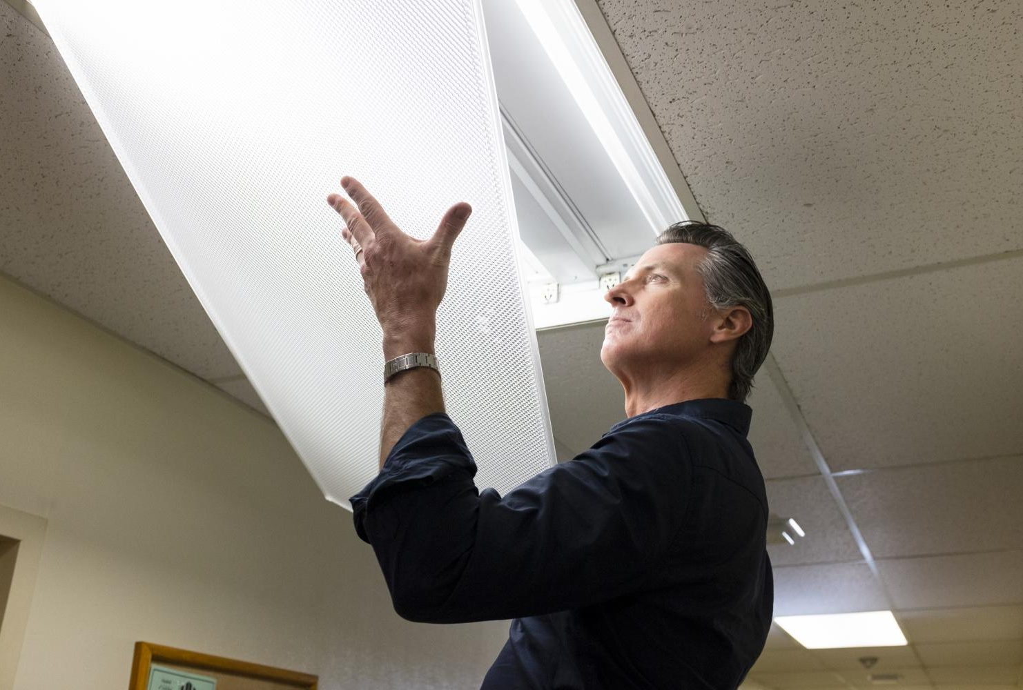 Gavin Newsom reattaches a light cover in Davies Hall at American River College after replacing two flourescant bulbs. While replacing the plastic cover Newsom accidentally cracked one corner. (Photo by Patrick Hyun Wilson)