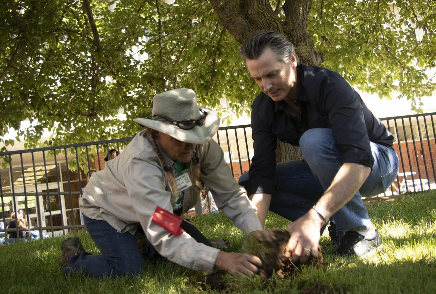 Governor Gavin Christopher Newsom assist American River College groundskeeper Brenda Baker with fixing the sprinkler at American River College during International Workers' Day on May 1, 2019. (Photo by Ashley Hayes-Stone)