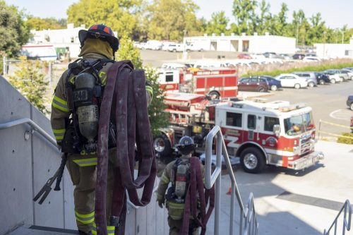 Firefighters Jake Bartlett and Gabriel Gomez carry fire hoses down from the top level of the American River College parking structure on Sept. 17, 2019. Sacramento Metro Fire District engines 24 and 103 ran drills testing the structure's standpipe water system, which they would use in the event of a fire within the parking garage. (Photo by Jennah Booth)