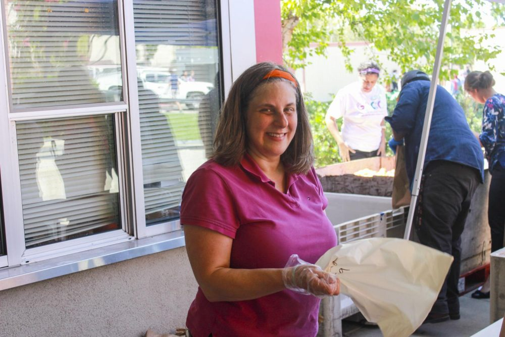 Volunteer Alicia Dienst hands out food to teachers and students for the Beaver Food Pantry on Aug. 28, 2019 at American River College.