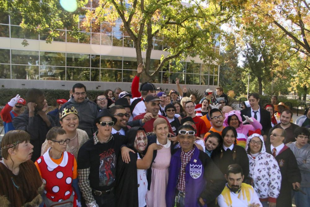 Ashley Guletz, program coordinator of the Aim Higher daycare center for adults with disabilities, gathers with clients after performing in a flash mob in front of the library at American River College on Oct. 31, 2019. (Photo by Alexis Warren)