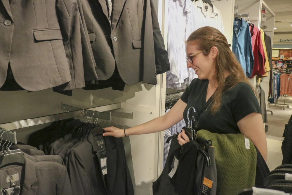 Sign language interpreting major and speech language pathology assistant Marissa Lang looks at blazers at the Suit Up event in JCPenney at Arden Fair Mall on Sept. 22, 2019. (Photo by Alexis Warren)