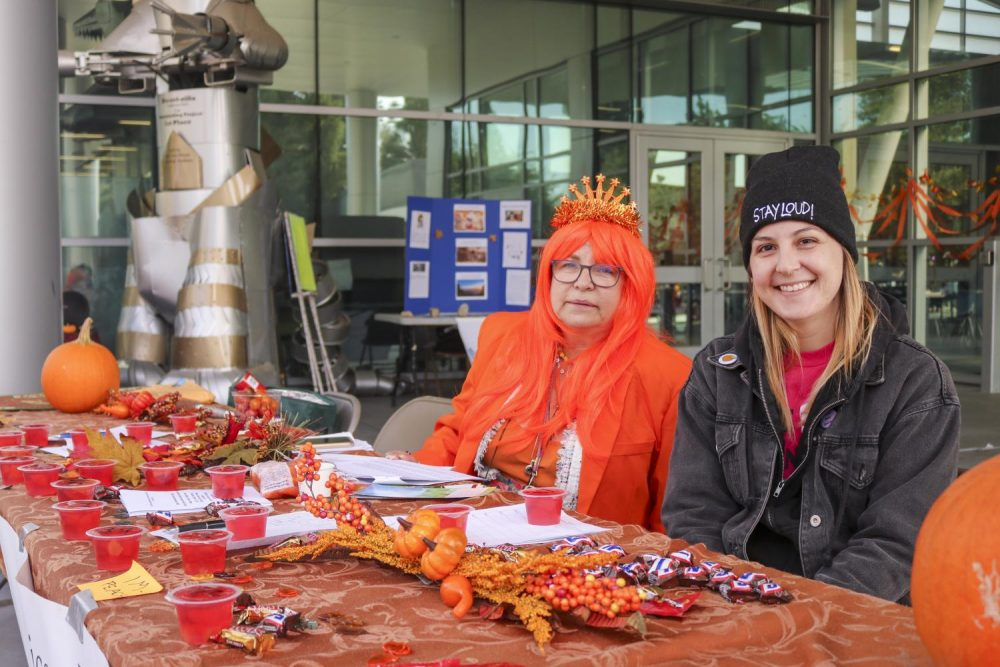 """Laurie Jones and Caitlin Lebas (left to right),presidents of the sociology club, participate in the Fall Harvest Club Day event by handing out their club information, candy and jello """"Impeaches"""" cups at American River College on Oct. 10, 2019. (Photo by Oden Taylor)"""