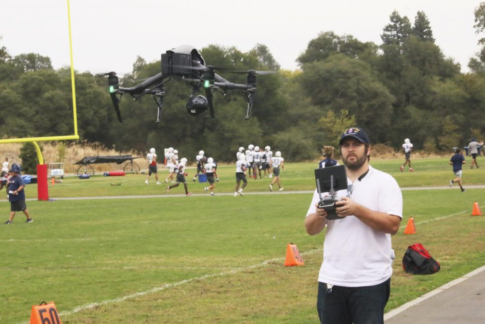 Dan Reid launches a drone to film a few periods of football practice at American River College on Oct. 16, 2019. (Photo by Jack Harris)