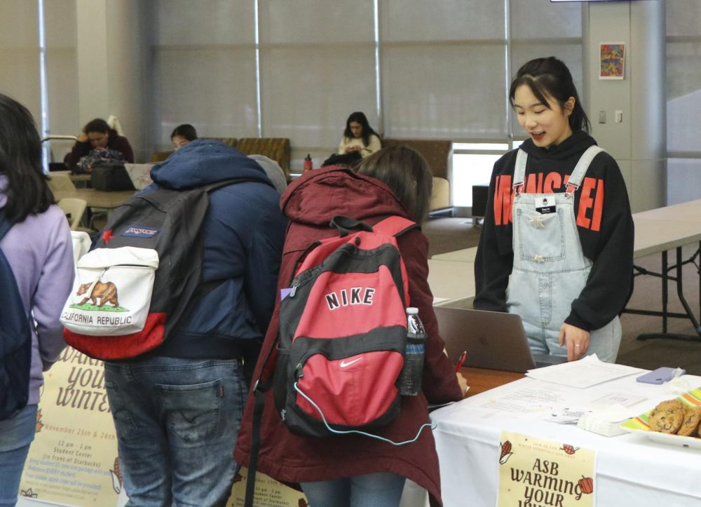 Fang Liu, an economics major and ASB Senator, helps students get warm clothes and first aid kits it the Student Center at American River College on Nov. 26, 2019. (Photo by Joshua Ghiorso)