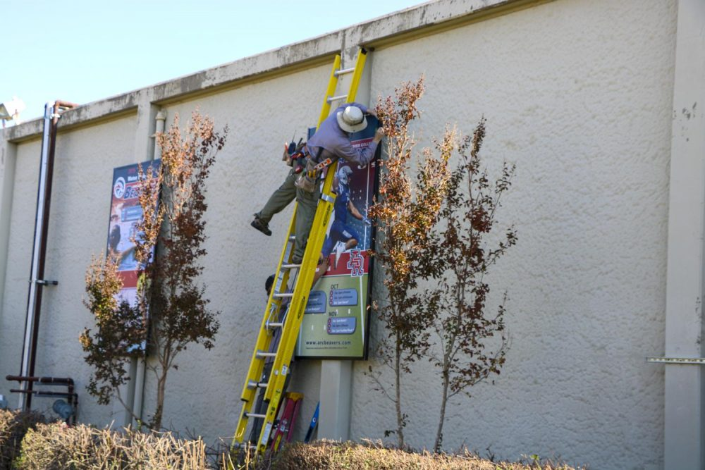 Construction workers hang posters on the gym wall advertising a variety of sports programs at American River College on Nov. 4 2019. (Photo by Colin Bartley)