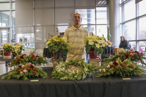 Carlos Goudeau assist with the floral sale that's put on by the HORT 201 floral design class that features holiday floral centerpieces along with potted plants in the Student Center at American River College on Dec. 12, 2019. (Photo by Brandon Zamora)