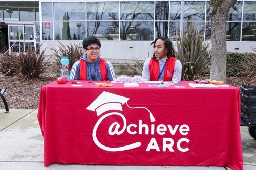 In front of  the American River College Library on Jan. 22, Nursing major Von Vega (left) and Psychology major Joaquin Holland (right), Student Support for Achieve at ARC, are ready at their table and eager to help the new students. (Photo by Bram Martinez)