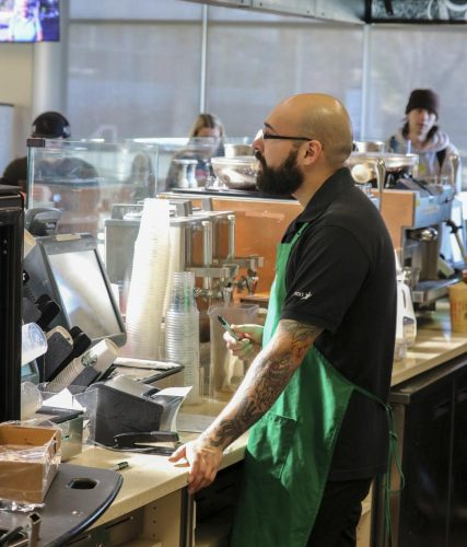 Alfonso Gonzales assists a customer at Starbucks in the Student Center at American River College on Jan. 30, 2020. (Photo by Haven Bishop)