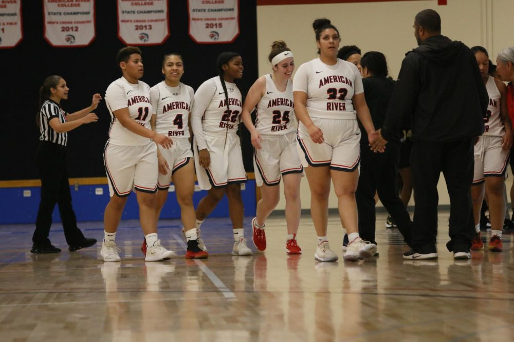 American River Collge women's basketball team congratulates Jordyn Hilliard after a made basket against San Joaquin Delta College on February 11, 2020. (Photo by Heather Amberson)