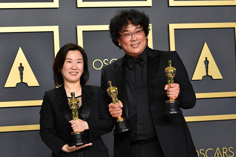 Bong Joon Ho and Kwak Sin Ae pose with their awards at the Oscars. (Photo Courtesy of IMDB).