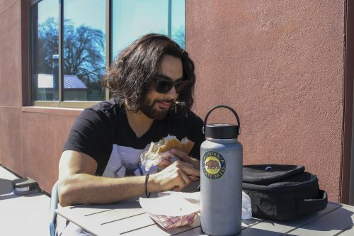 Ecology major Josh Moreno enjoys a salami sandwich outside American River College's Oak Cafe Bakery on Feb. 26 , 2020.(Photo by Brandon Zamora)