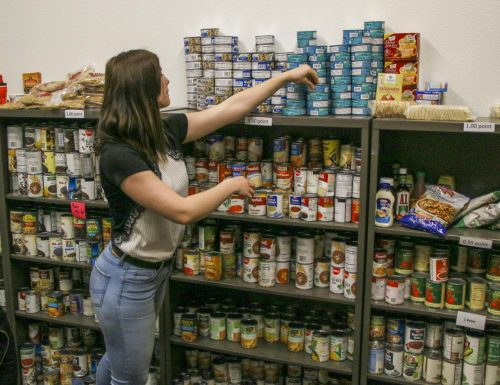 Ana Radu, Student Support Specialist of the Beaver Food Pantry, manages inventory of canned goods at American River College on March 2, 2020. (Photo by Clifton Bullock)