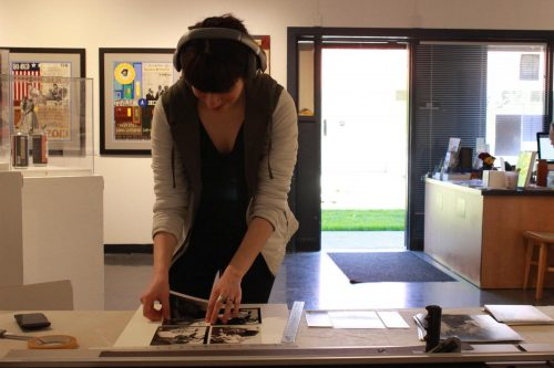 Studio Art major, Diana Ormanzhi is at a table in the Kaneko Art gallery on March 10, 2020, preparing silver gelatin mattering photos to be posted. (Photo by Marquala Brown)