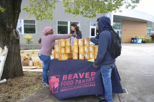 Mariama Bah and Ana Radu, student support specialists for the American River College Beaver Food Pantry, distribute cheddar flavored Blue Diamond Nut-Thins to students on March, 17 2020. This will be the last day that the food pantry will operate before the campus closes indefinitely due to the COVID-19 pandemic.  (Photo by Oden Taylor)