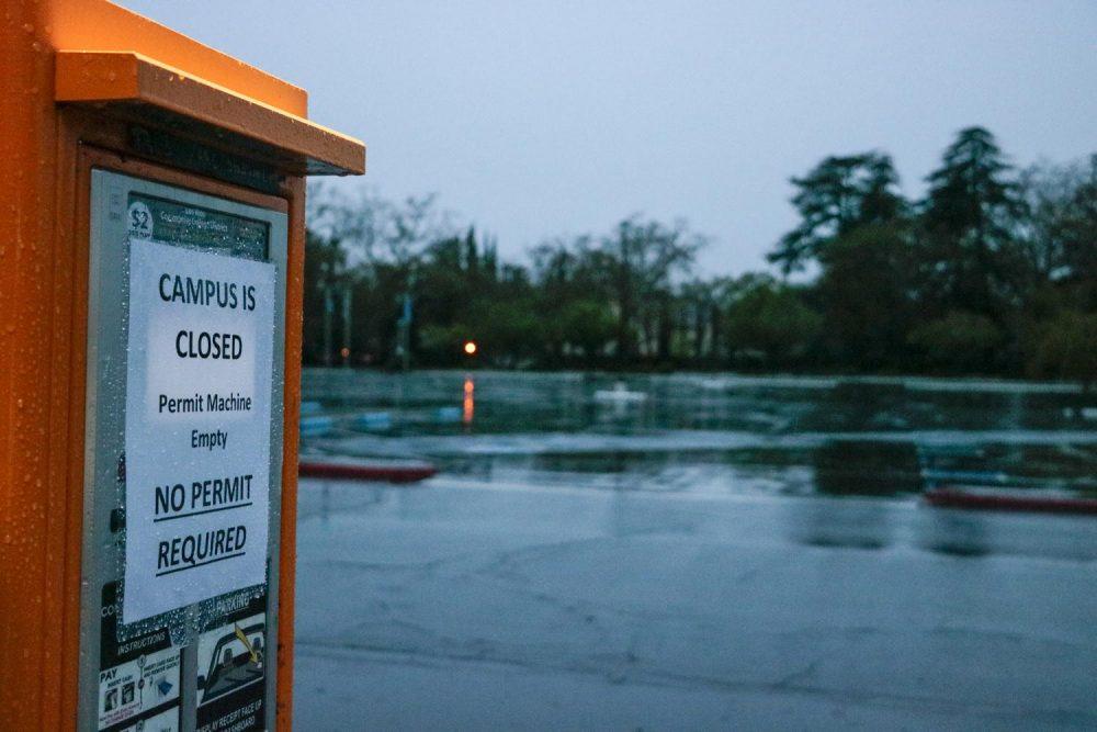 A sign that reads 'Campus Is Closed No Permit Required' hangs on the ticket kiosk in an empty parking lot at American River College on March 16, 2020. Since the Los Rios Community College closed its campuses, students' classes are now converted to online until further notice.