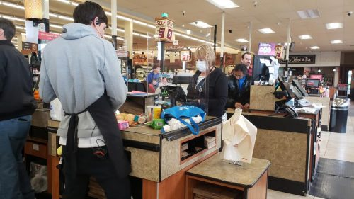 A grocery worker checks out a customer at a Raley's in Carmichael, Calif. on March 20, 2020. With residents in Sacramento living under quarantine, only essential businesses like Raley's Supermarkets are open while taking protective measures. (Photo by Ashley Hayes-Stone)