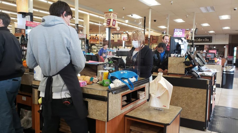 A grocery worker checks out a customer at a Raleys in Carmichael, Calif. on March 20, 2020. With residents in Sacramento living under quarantine, only essential businesses like Raleys Supermarkets are open while taking protective measures. (Photo by Ashley Hayes-Stone)